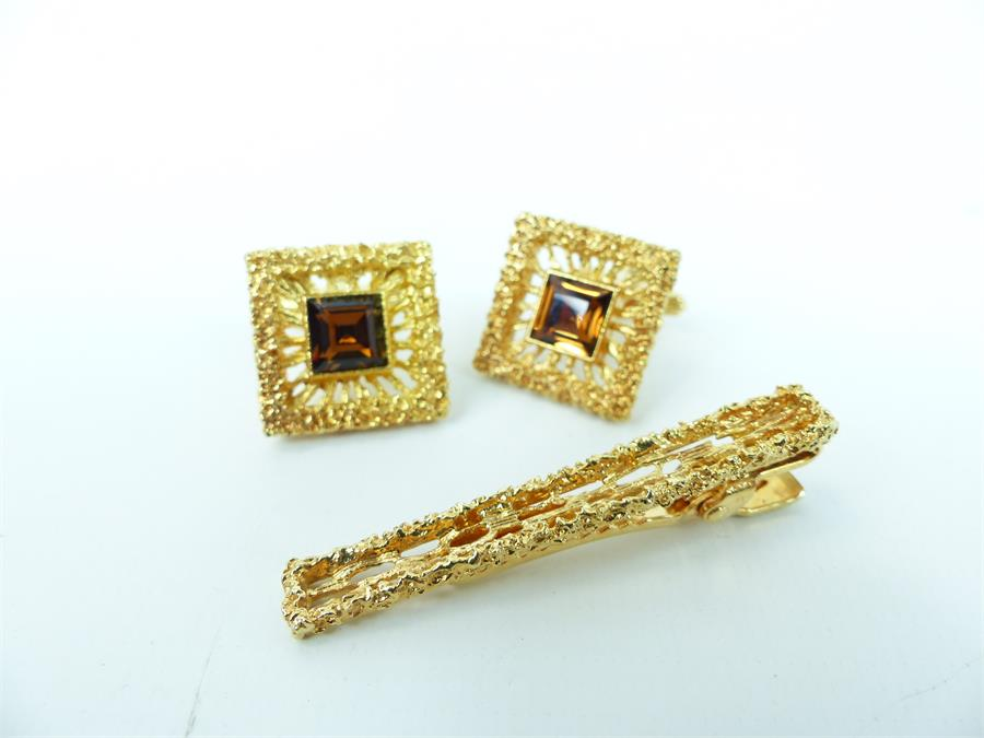 Lot 48 - A pair of gold plated cufflinks and a tie bar