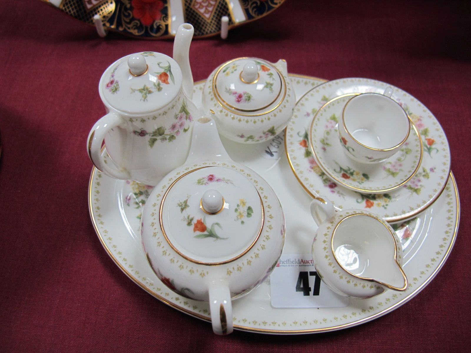 Lot 47 - A Wedgwood Bone China Miniature Four Piece Tea Set, matching trio and oval tray. (8)