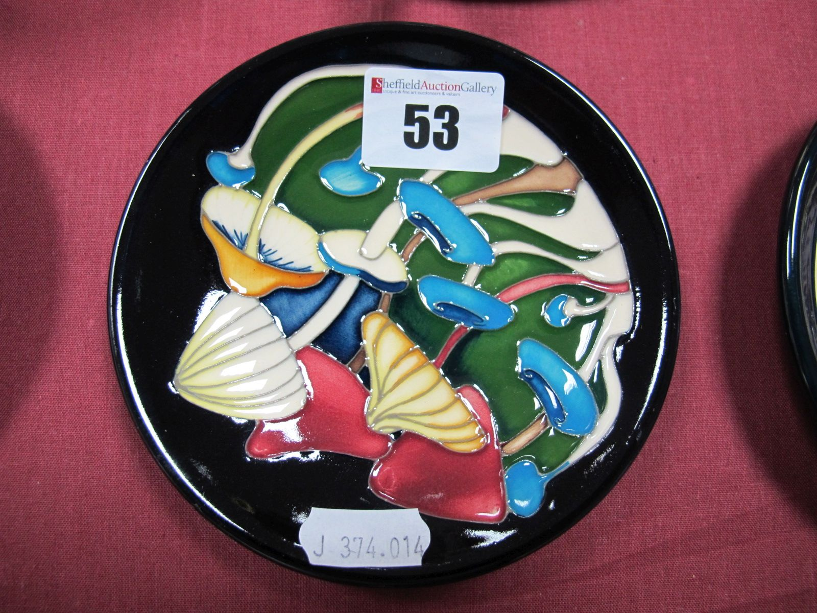 Lot 53 - A Moorcroft Pottery Coaster, decorated with the 'Pixie Parasols' design by Emma Bossons, shape 780/