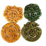 WITHDRAWN- Four Chinese hardstone pendants, decorated with dragons and scrolling folia