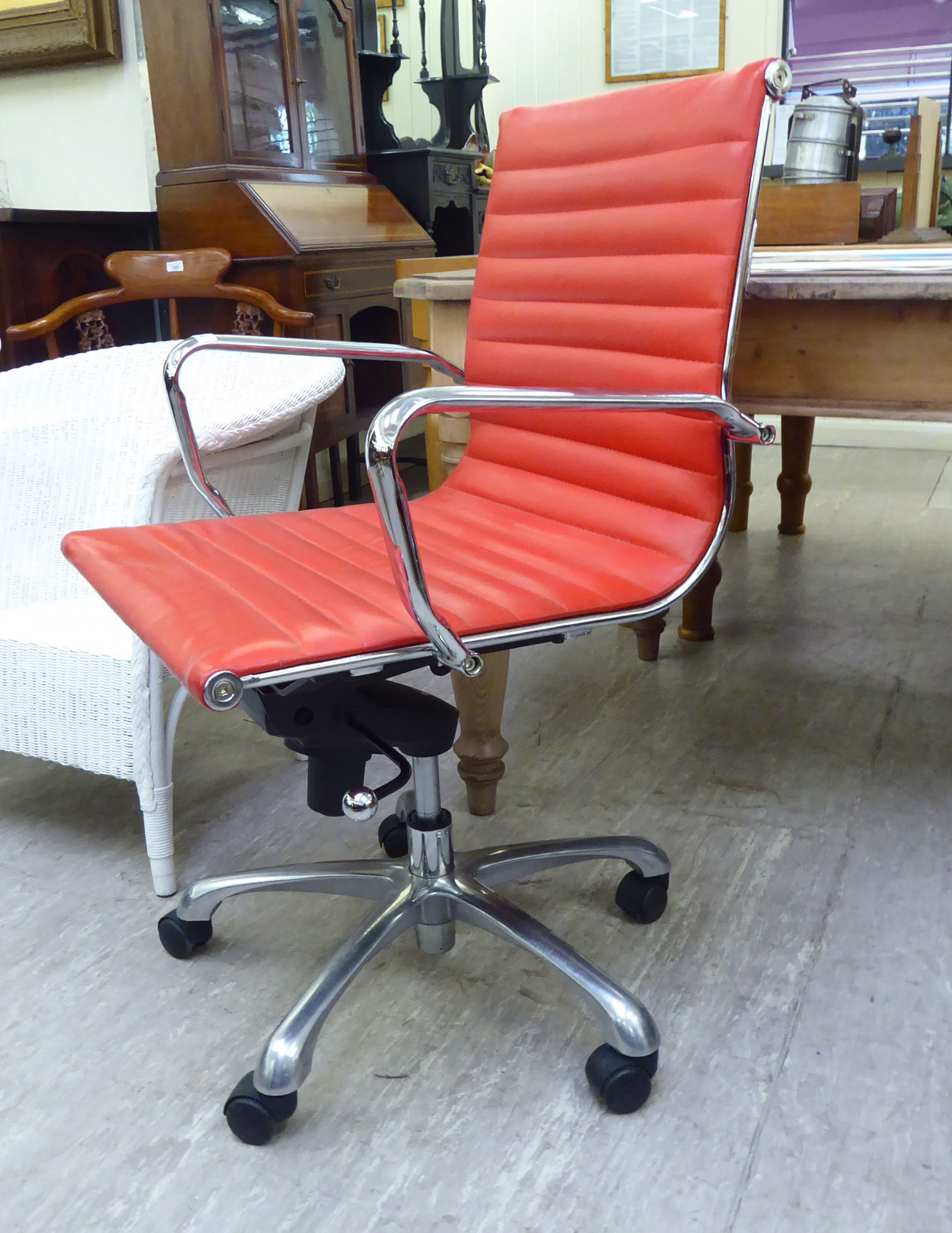 Lot 108 - A modern desk chair, the chromium plated frame with a stitched red hide cushioned back and seat,