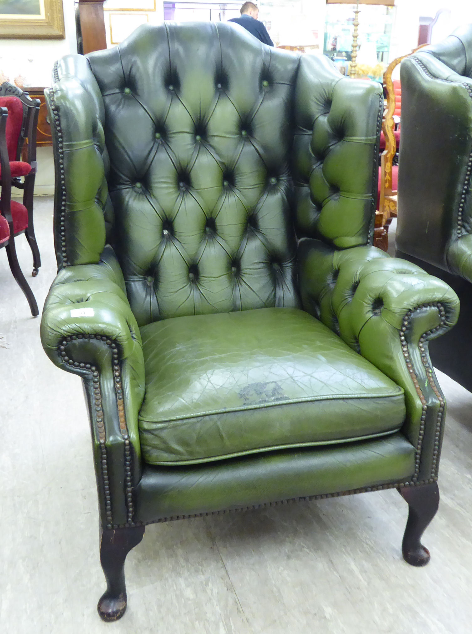 Lot 94 - A mid 20thC Georgian style wingback part buttoned and stud green hide,