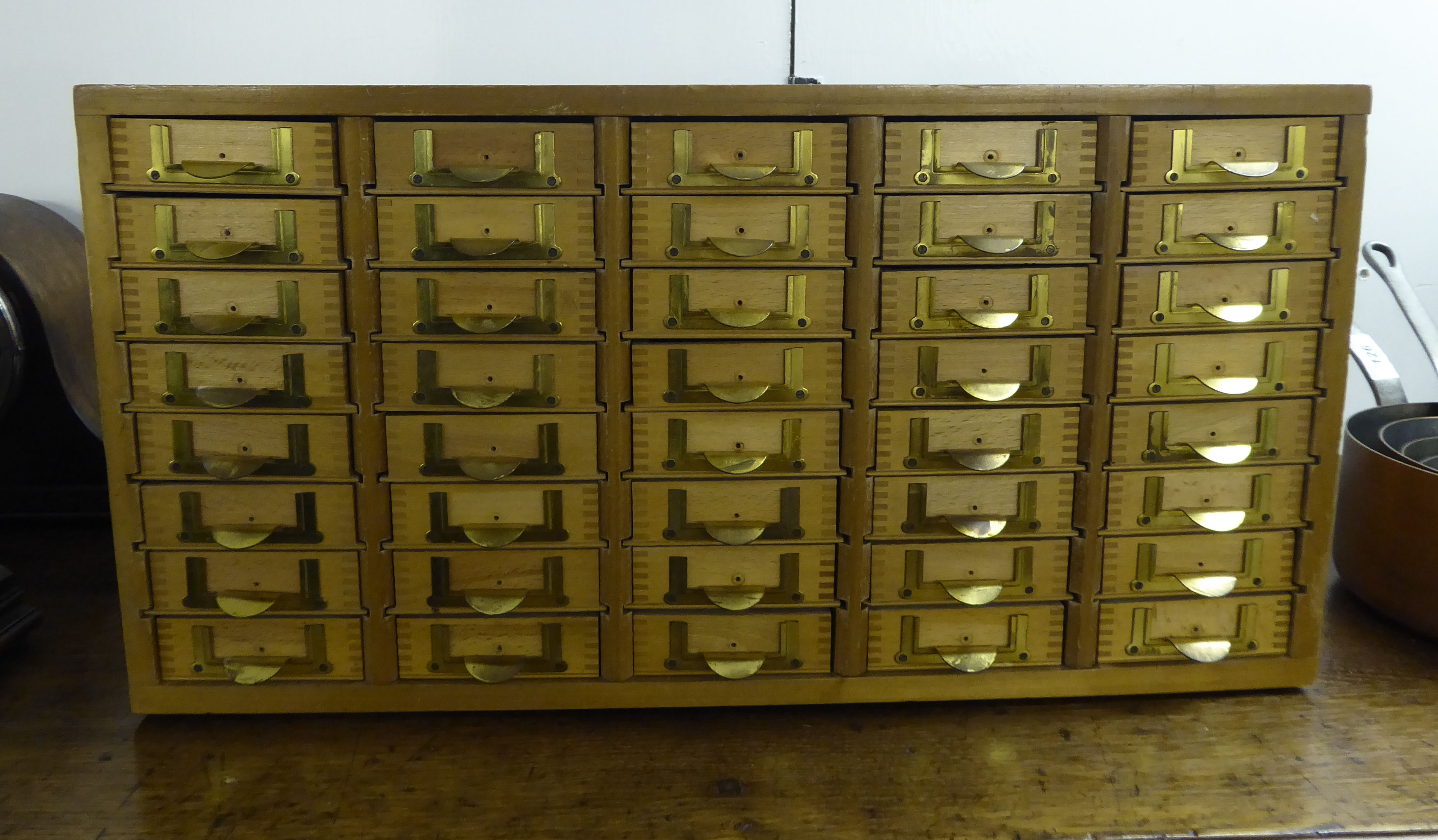 Lot 99 - An Emir of Ashford teak and pine finished table-top filing cabinet with forty drawers,