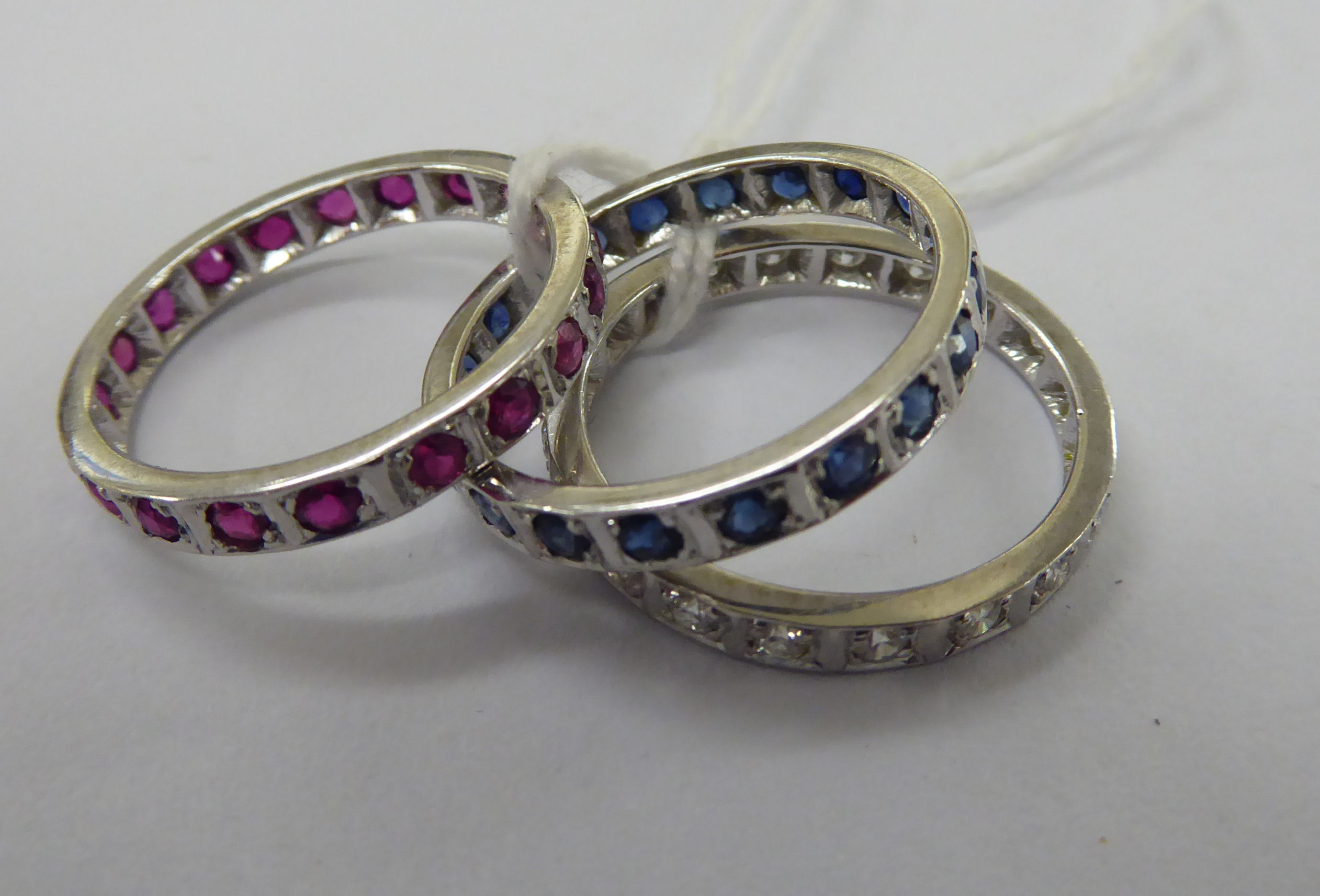 Lot 43 - Three white metal eternity rings, respectively set with diamonds,