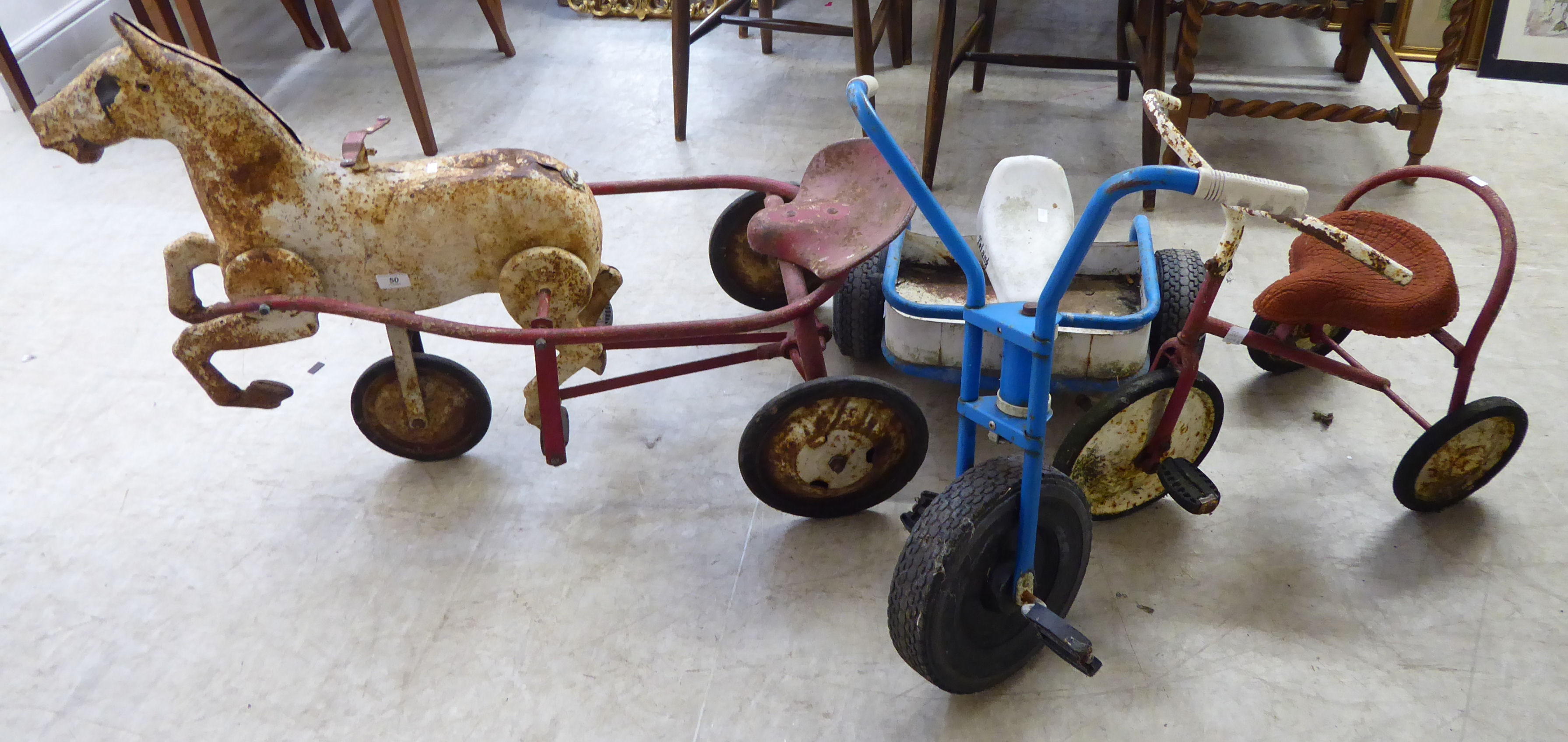 Lot 50 - Three Tri-ang ride-on toys: to include a tricycle BSR