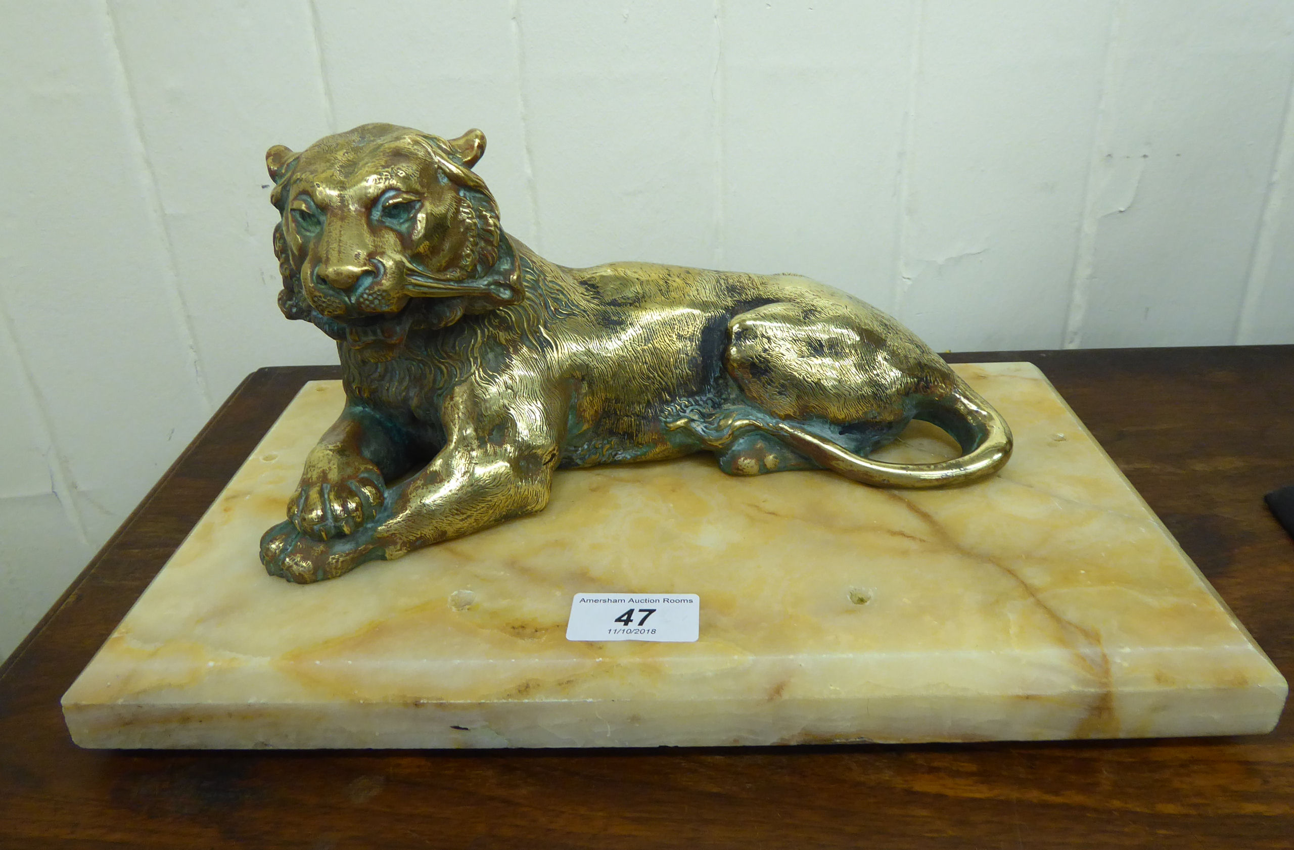 Lot 47 - An early 20thC lacquered brass inkwell, fashioned as a seated lioness,