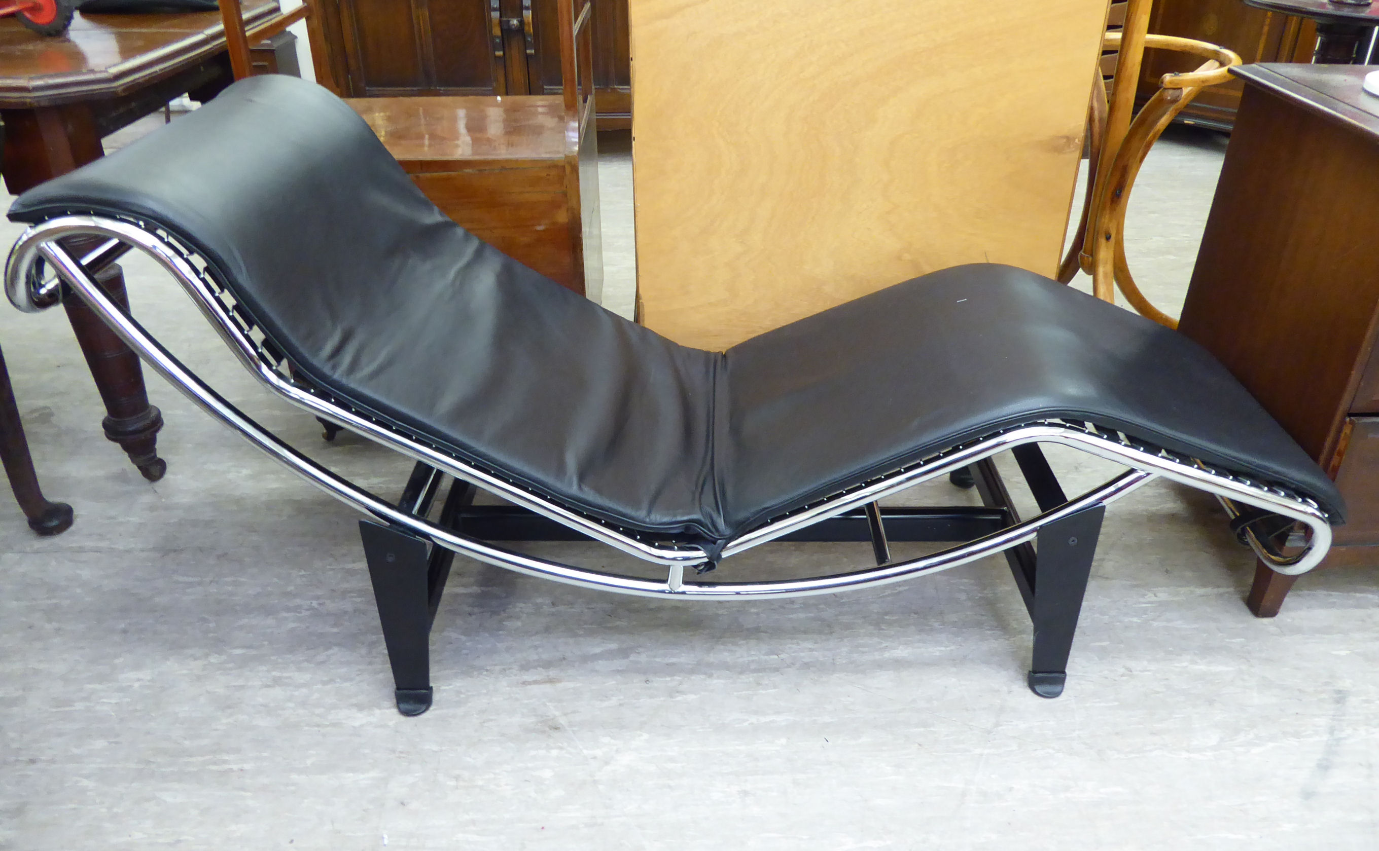 Lot 78 - A designer day bed/chair, the chromium plated frame with a black hide cushioned seat,