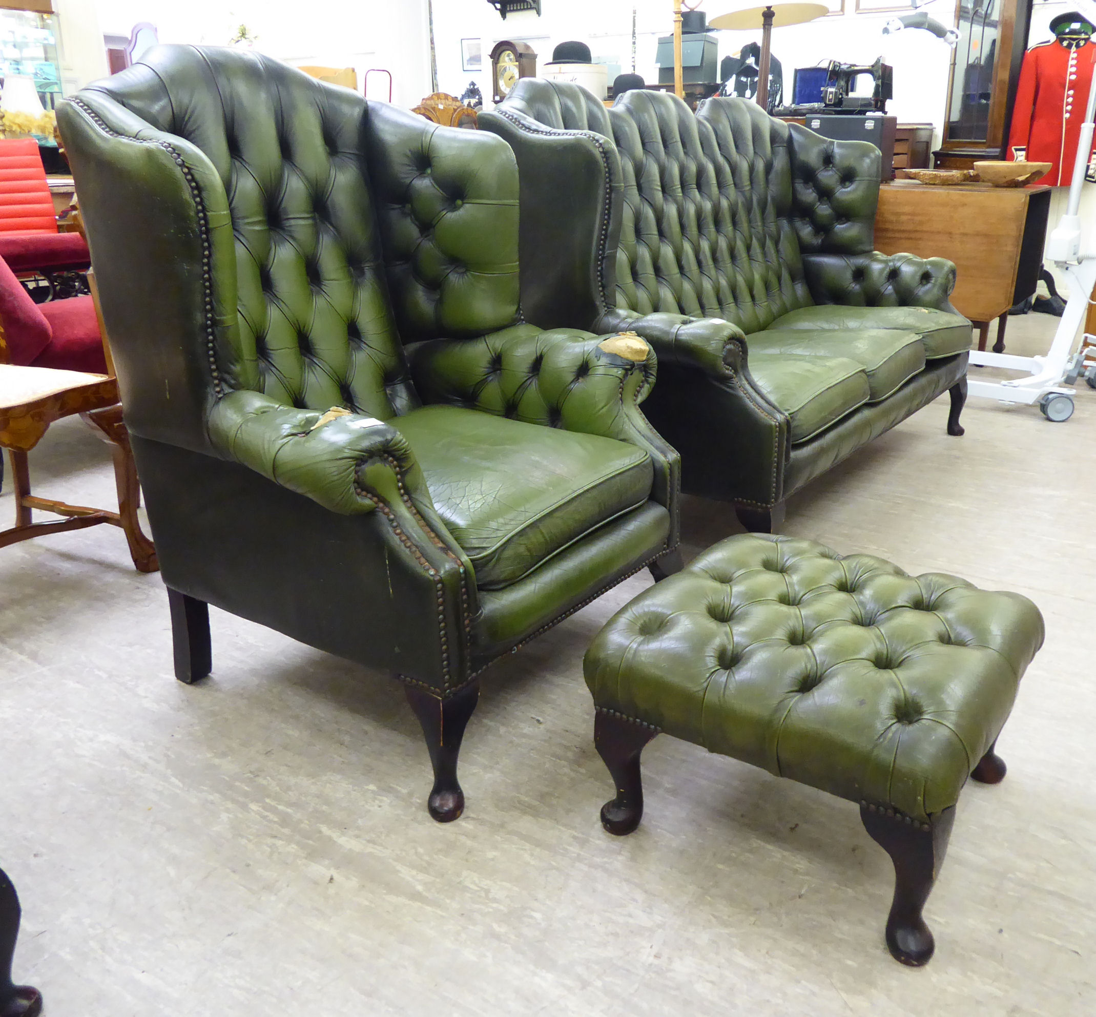 Lot 110 - A mid 20thC Georgian style wingback, part buttoned and stud green hide upholstered armchair,