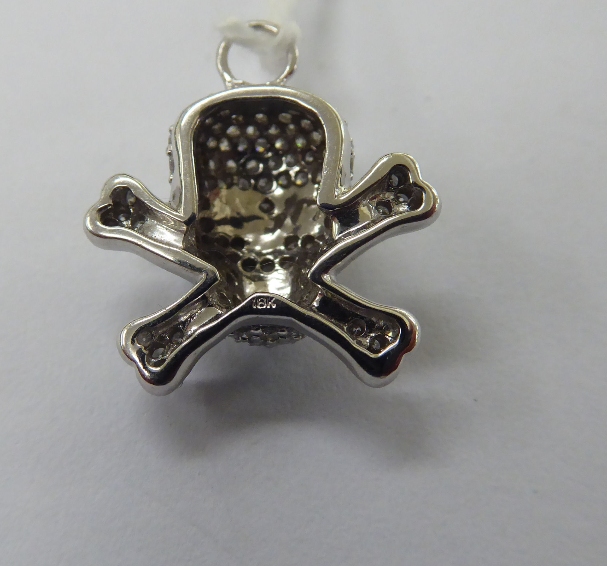 Lot 30 - An 18ct white gold skull and crossbones pendant,