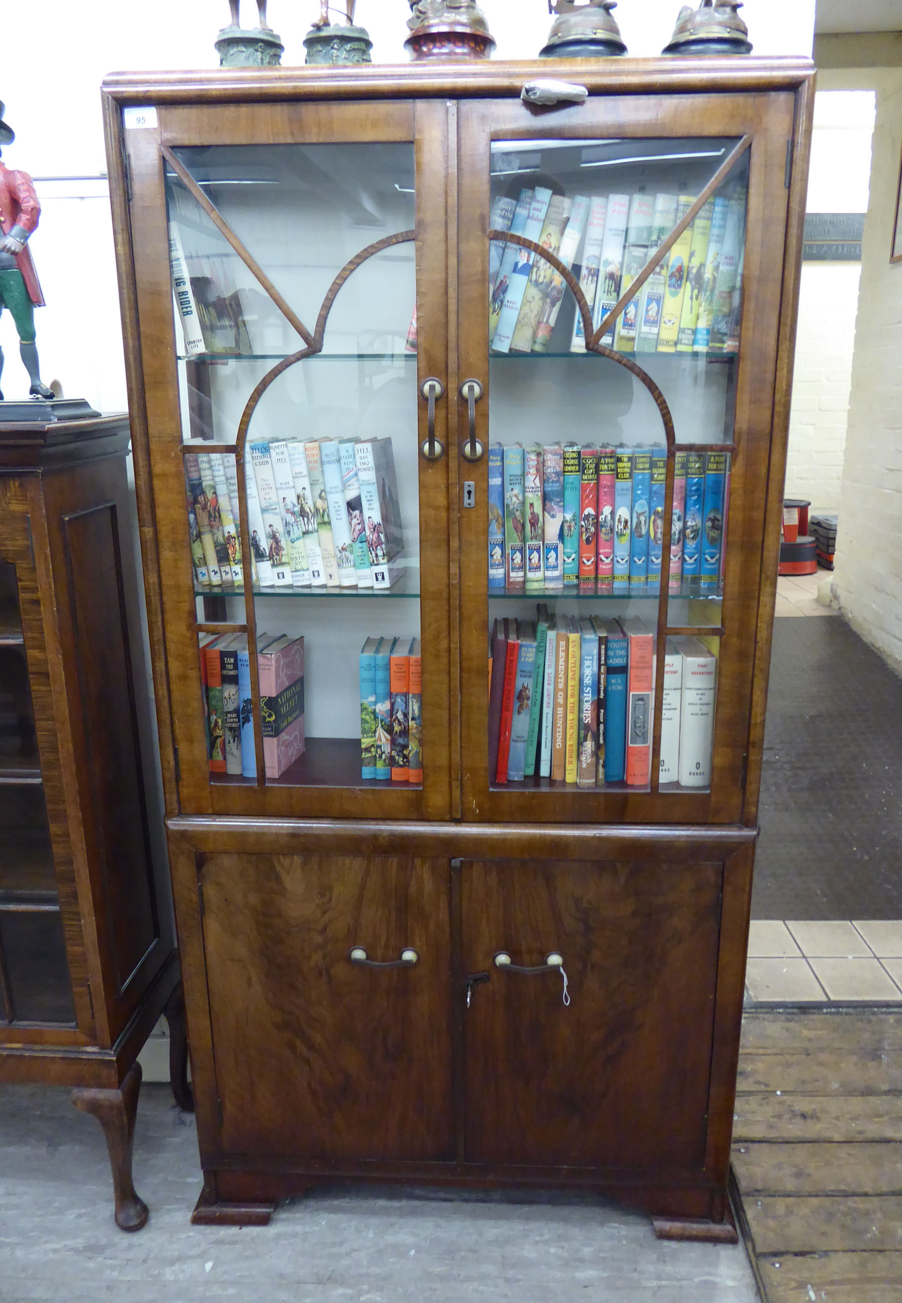 Lot 95 - An Art Deco crossbanded walnut finished display cabinet with a pair of glazed doors,