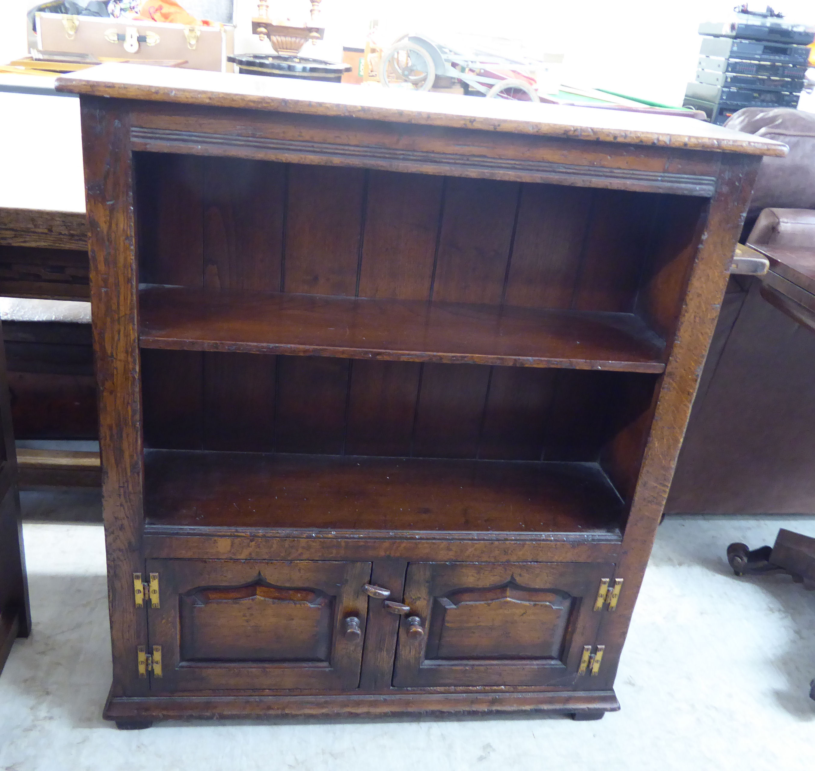 Lot 88 - A modern reproduction of an Old English style, stained oak bookcase with two open shelves,