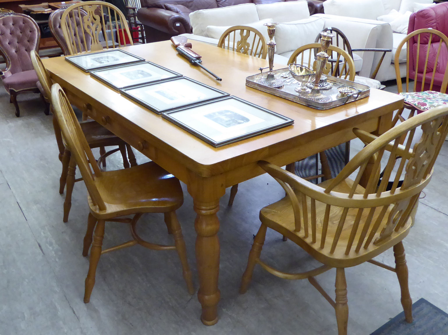 Lot 119 - A modern farmhouse style chestnut dining table, the top with round corners, over six frieze drawers,