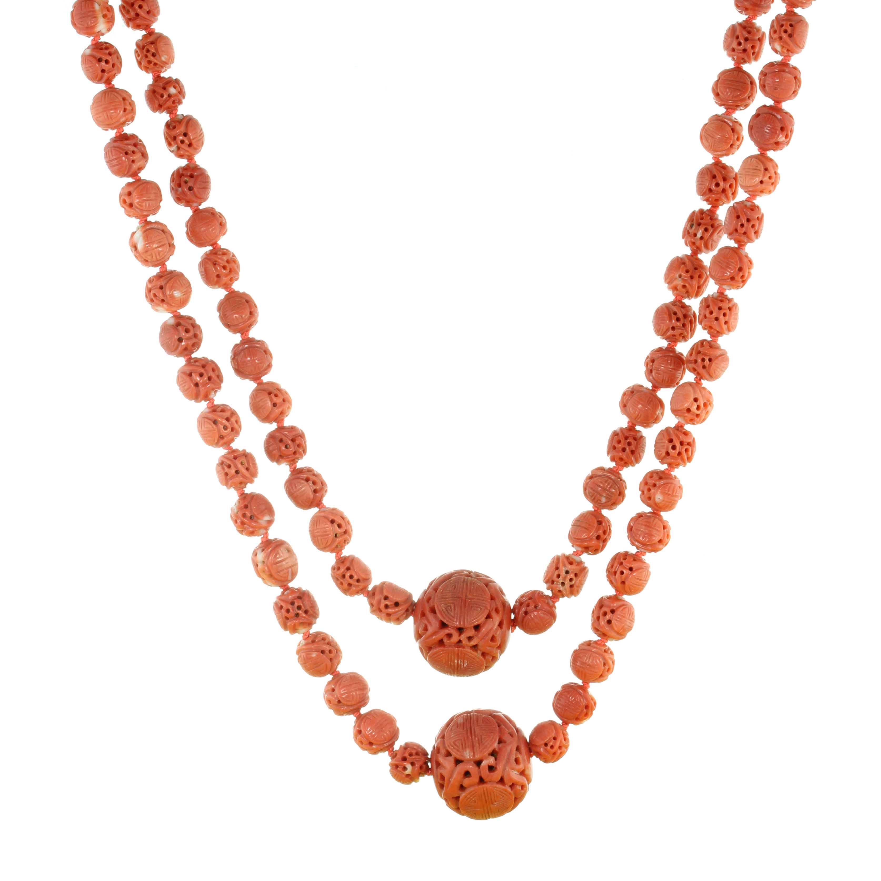 Los 19 - AN ANTIQUE CHINESE CARVED CORAL BEAD NECKLACE comprising four large beads of 21-24mm within a