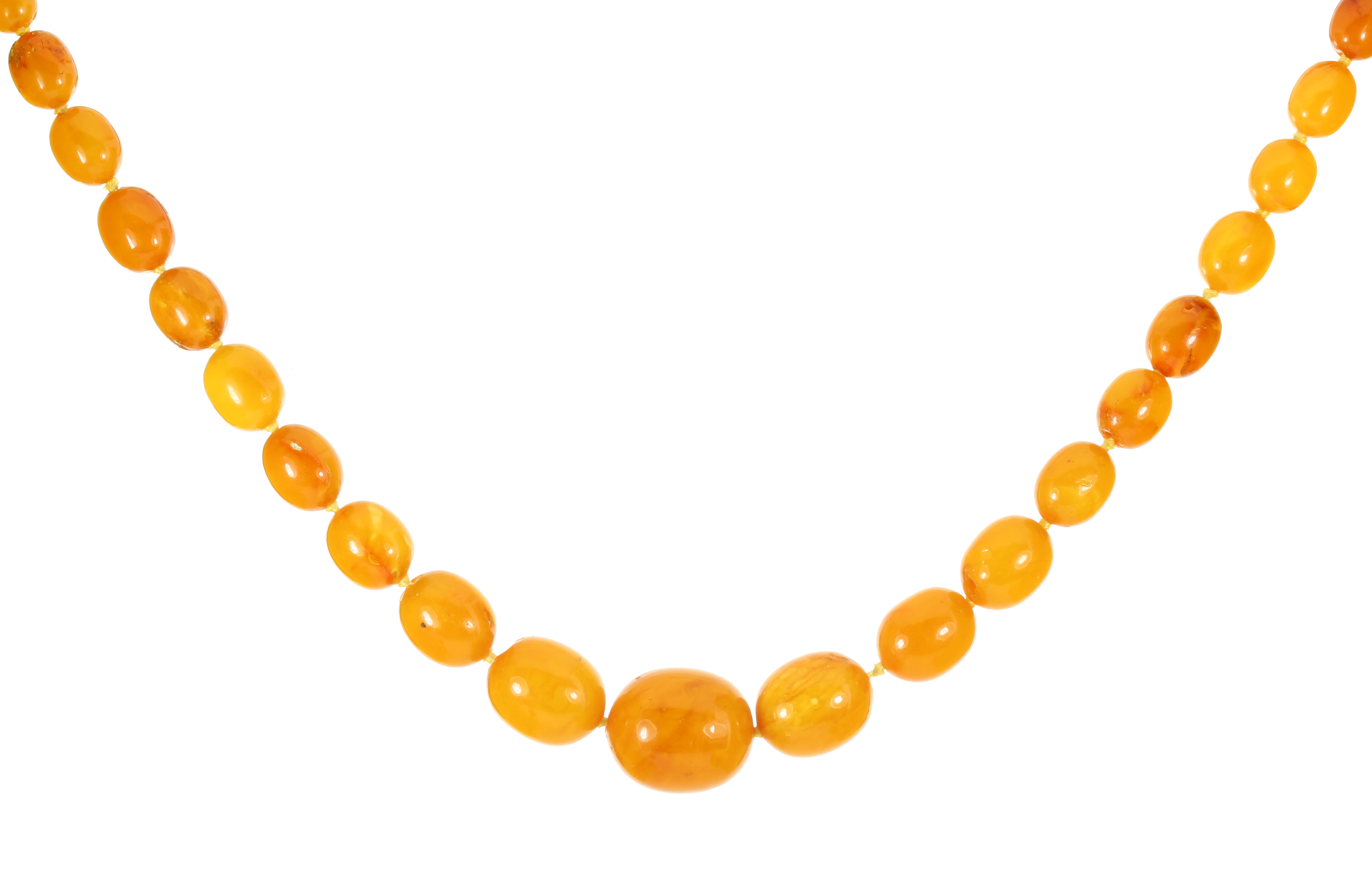 Los 4 - A NATURAL AMBER BEAD NECKLACE comprising a single row of forty-nine graduated polished oval beads up