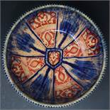 A Persian glazed ceramic bowl, the interior decorated with floral motifs, marked and dated to