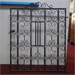 A vintage black painted wrought iron gate, 115 x 90cm