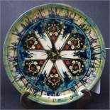 A Persian glazed ceramic dish, decorated with stylised floral motifs, marked and dated to base, H.