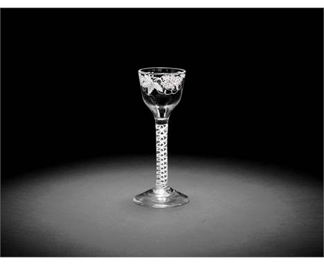 A Beilby enamelled opaque twist wine glass, circa 1765The ogee bowl painted with fruiting vine in opaque white, set on a doub