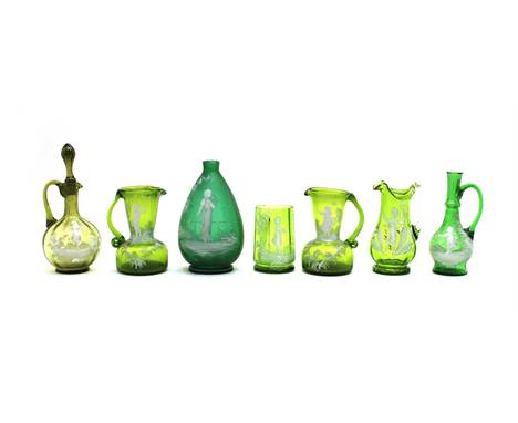 Ten pieces of green Mary Gregory glass, a vase, 16.5cm high, an oil carafe and stopper, 19cm high, four further jugs, two tum