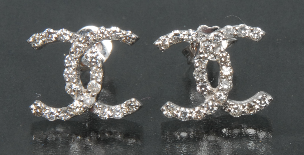 Lot 3062 - A pair of contemporary certified diamond Chanel style crossed Cs shaped earrings,