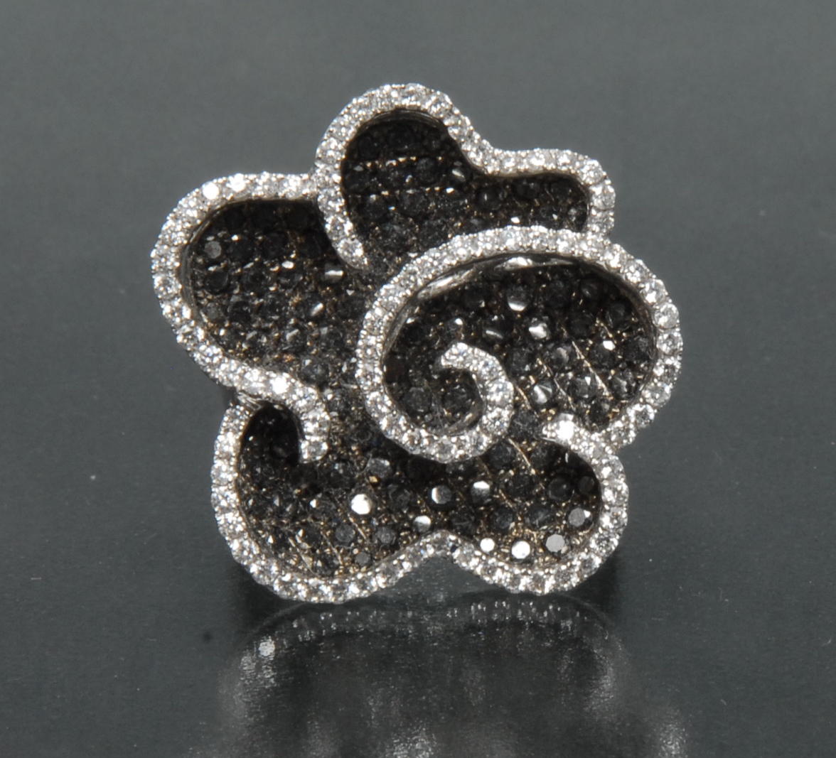 Lot 3050 - A contemporary certified fancy black and white diamond flower head dress ring,