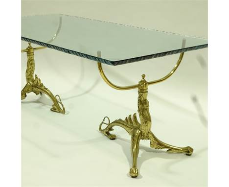 A 1970s' Italian coffee table, with twin brass dragon base supporting a thick glass top with flame polished fractured edge de
