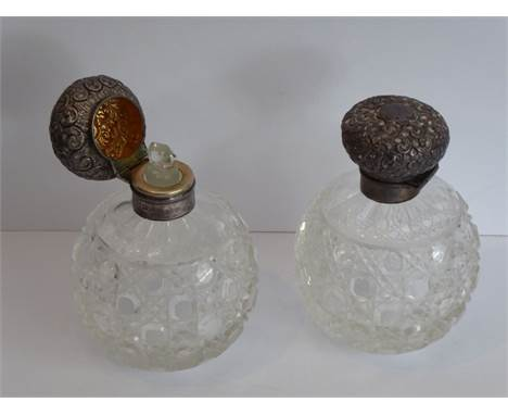 A pair of early 20th century spherical cut-glass silver-mounted scents; the hinged lids decorated in repoussé style with vaca