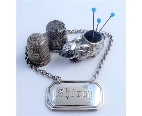 Two silver thimbles, a silver rabbit pincushion and a silver 'Sherry' decanter label(The cost ofUK postagevia Royal Mail Sp
