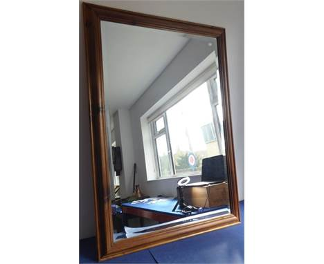 A modern wall-hanging looking glass; hand-bevelled plate withstained-pine frame (frame size 73cm x 104cm)
