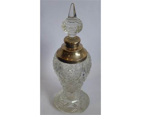 A cut-glass baluster-shaped scent bottle on spreading circular foot; the spire stopper above a silver-mounted neck (marks rub