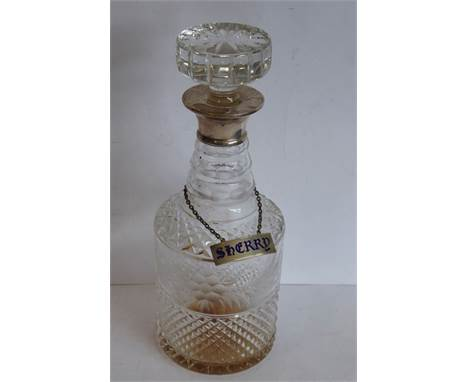 A cut-glass cylindrical decanter with mushroom-style stopper and hallmarked silver neck, also with hallmarked silver and enam