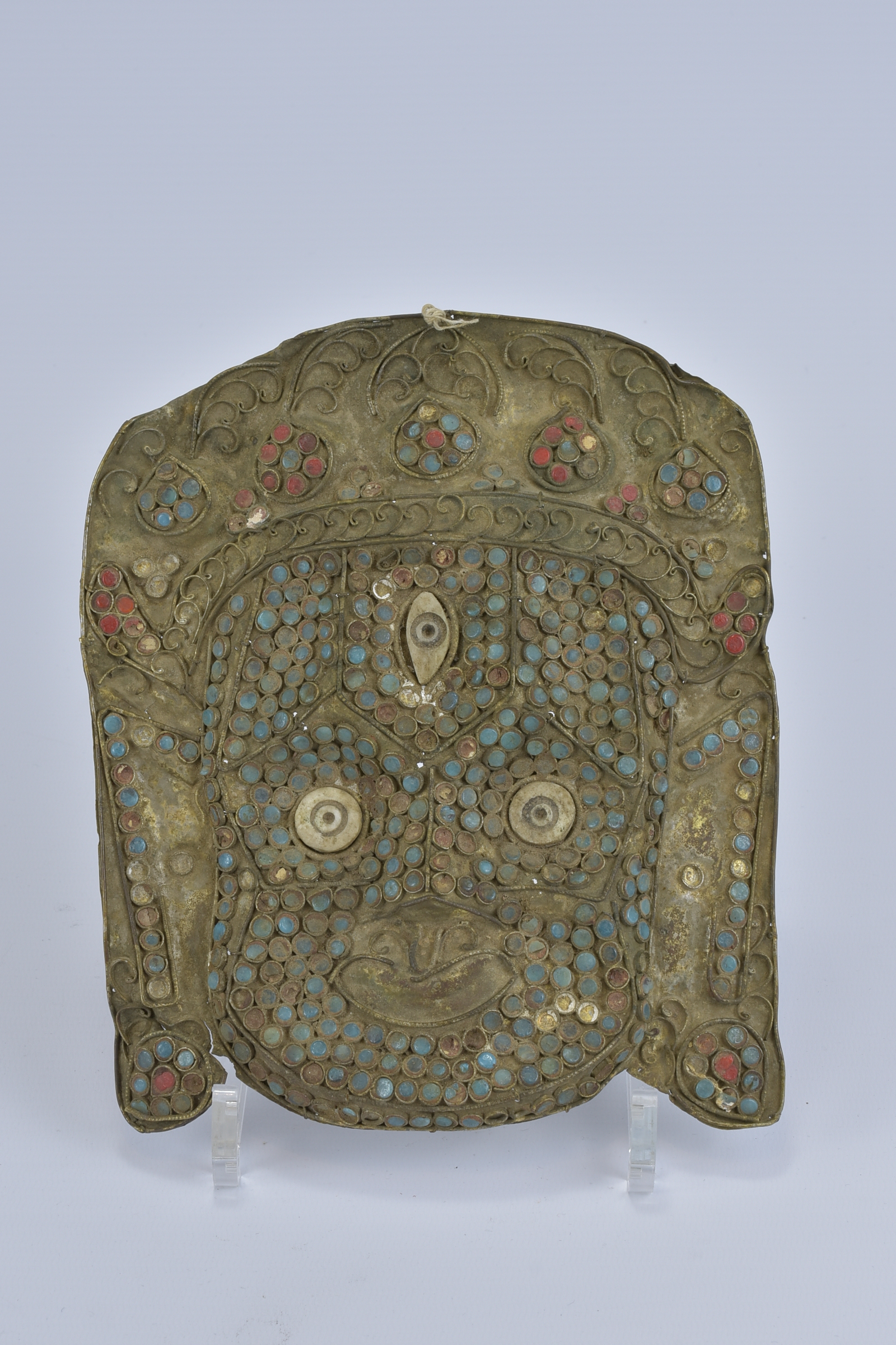 Lot 28 - A Tibetan metal mask fitted with coloured stone inserts. 20cm x 18cm