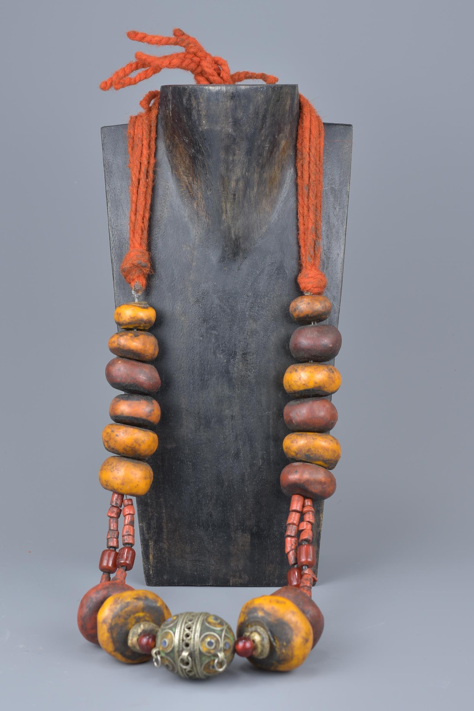 Lot 30 - A large Moroccan amber resin and coral bead necklace with enamel silver metal pendant.
