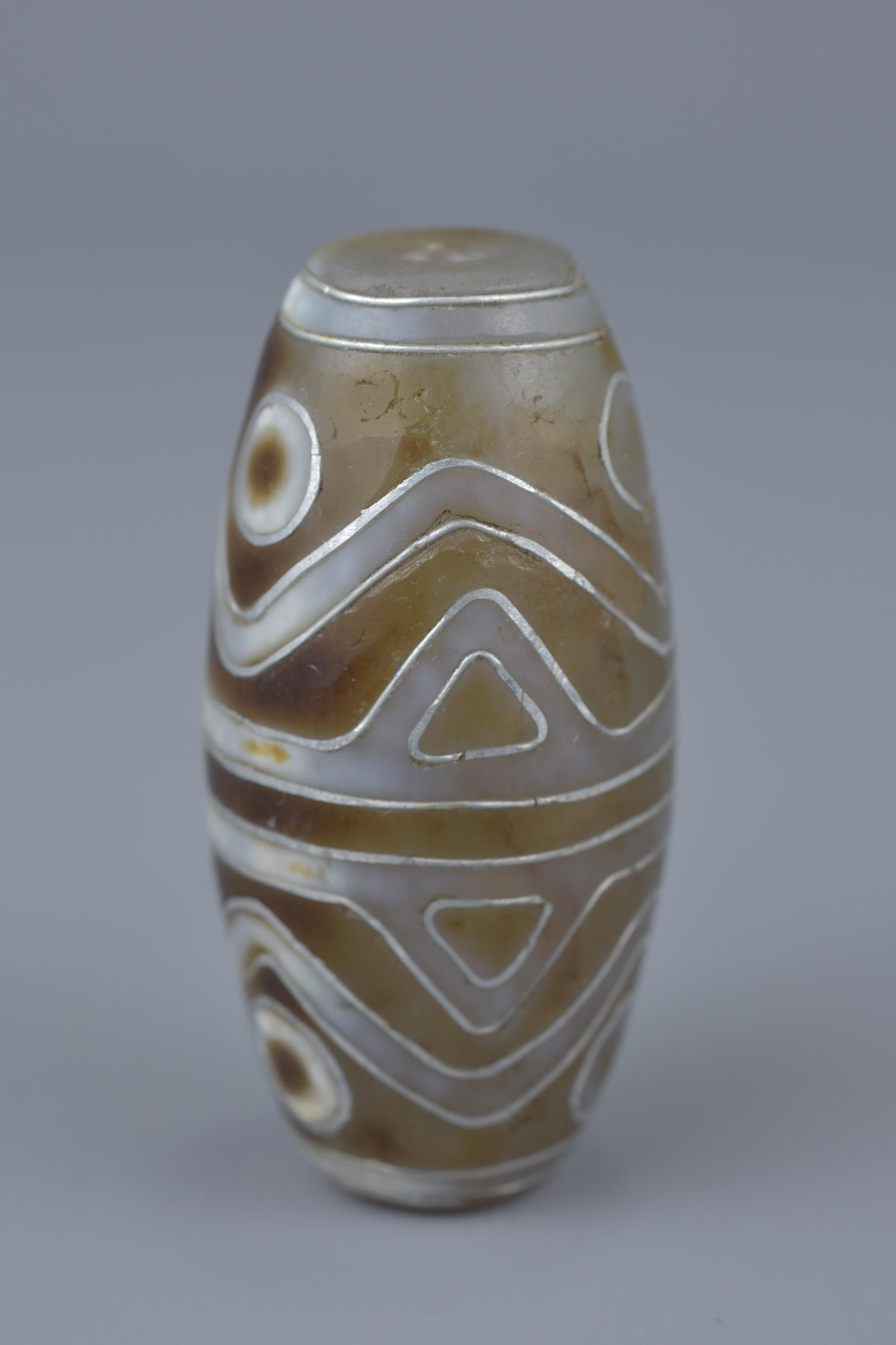 Lot 4 - A Tibetan agate bead Tianzhu style inlaid with silver.