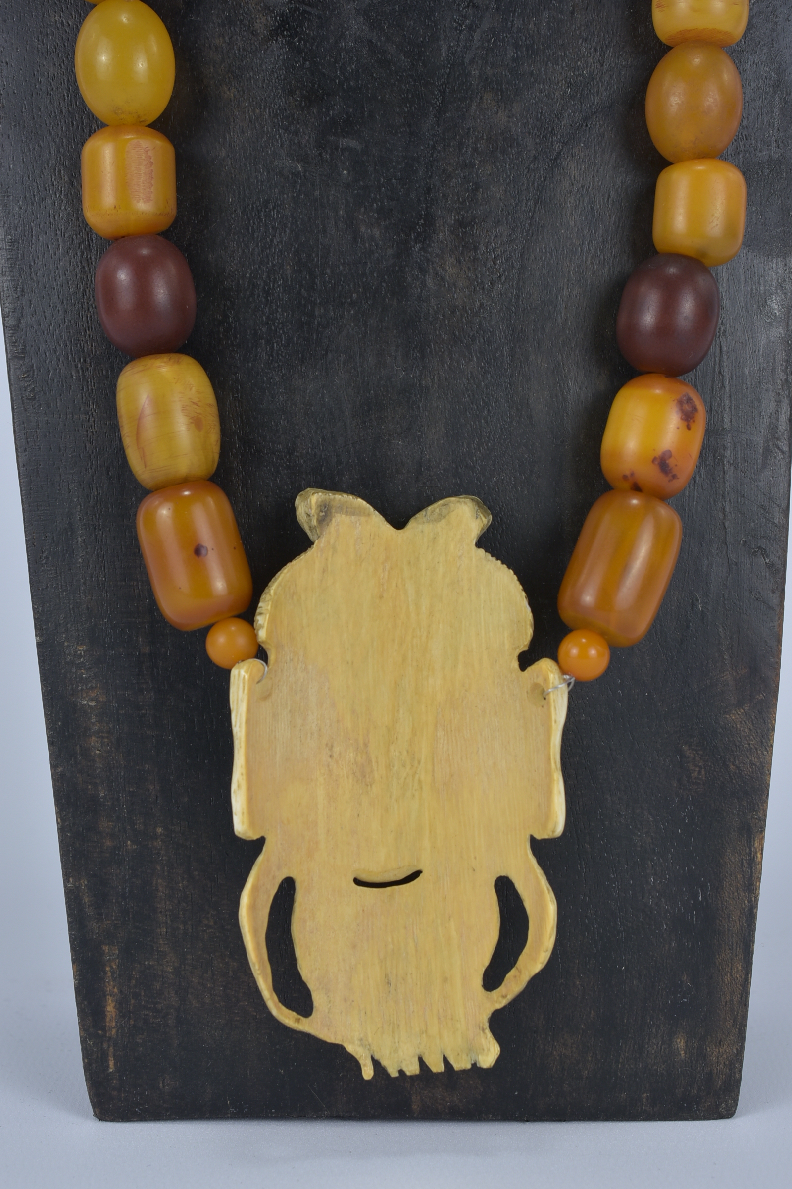 Lot 54 - An Ivory Pendant on Amber colour beaded necklace. Pendant 9cm  length.