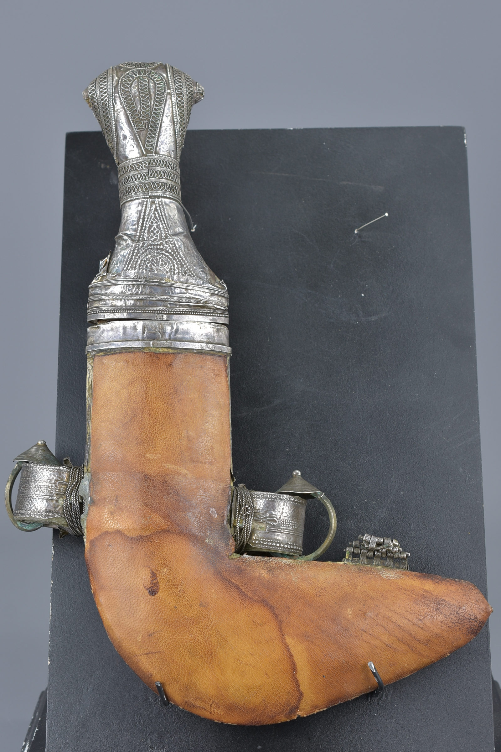 Lot 14 - A Yemenis silver-coloured metal dagger in a case on later display stand. 29cm length