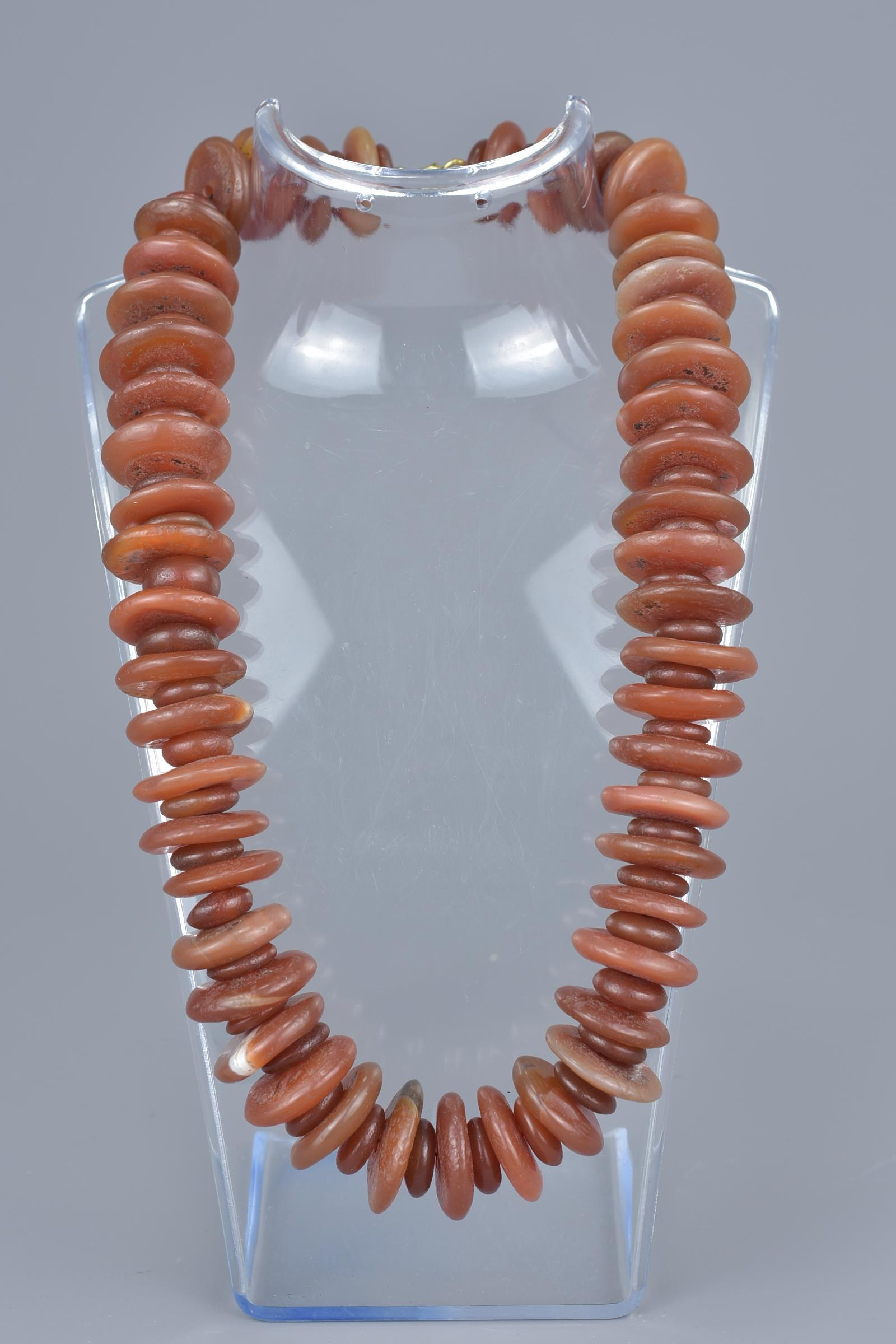 Lot 37 - A string of red agate beads in a necklace.