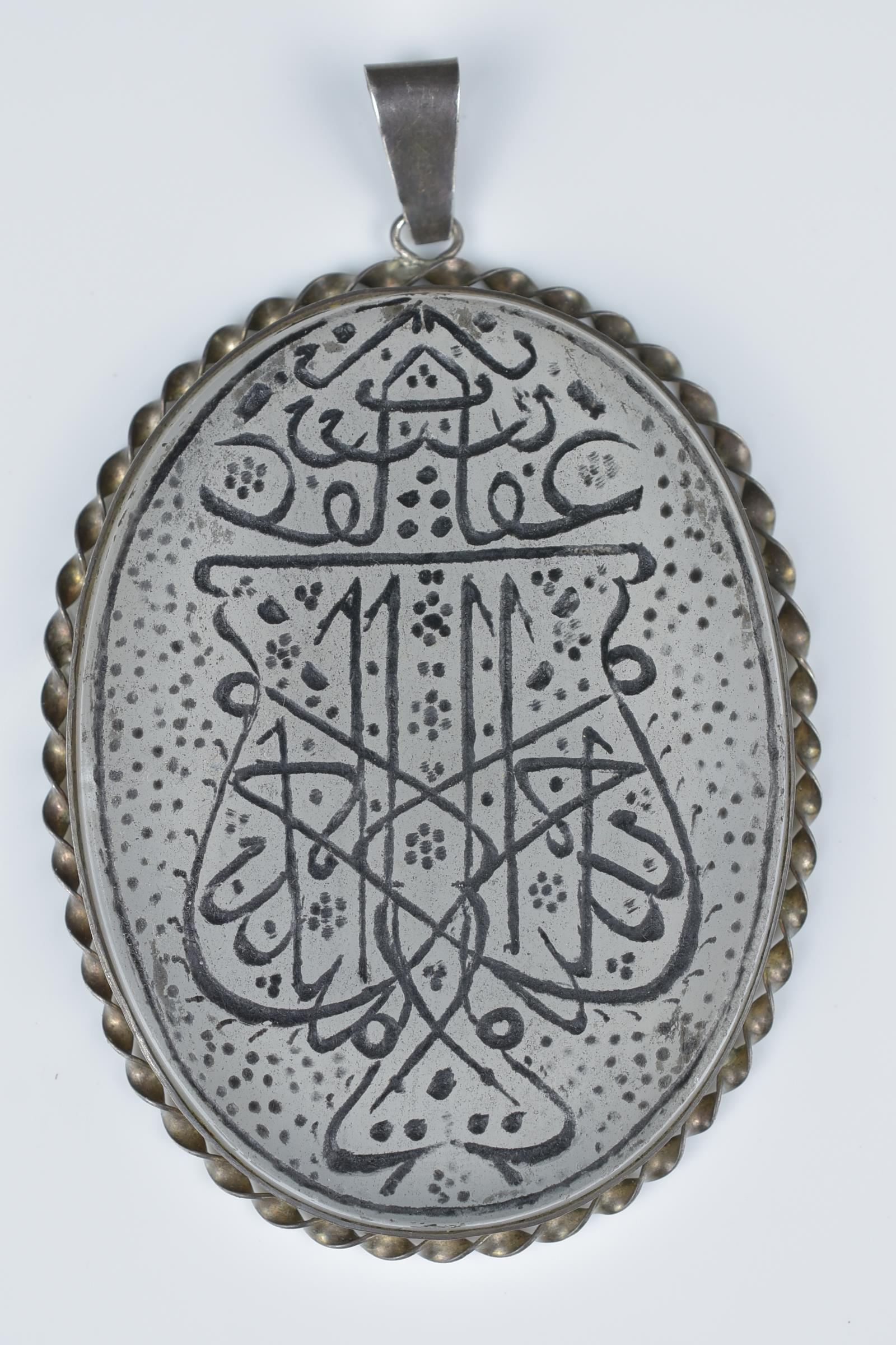 Lot 33 - A Persian white metal pendant with inscription.