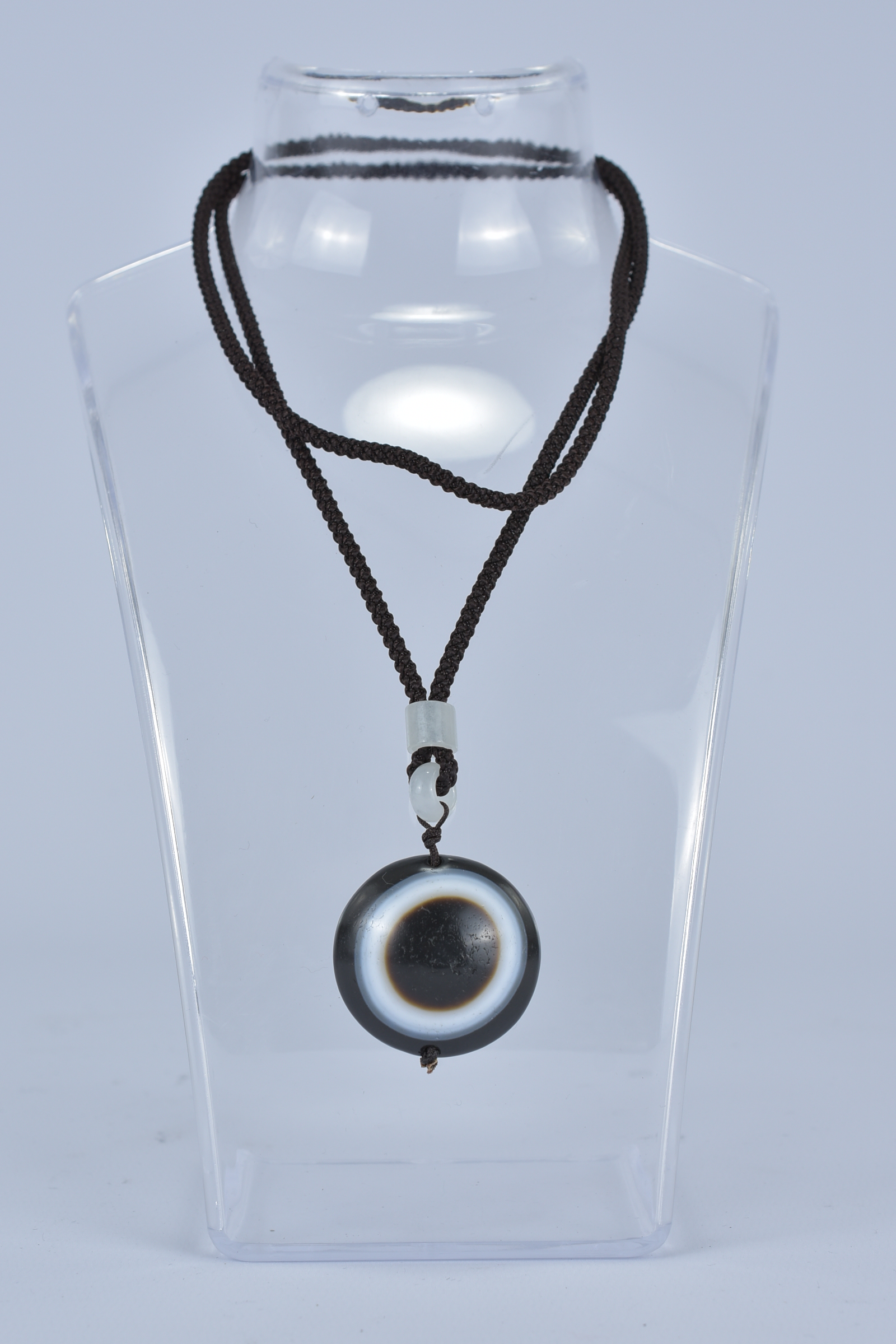 Lot 35 - A banded agate pendant on string.