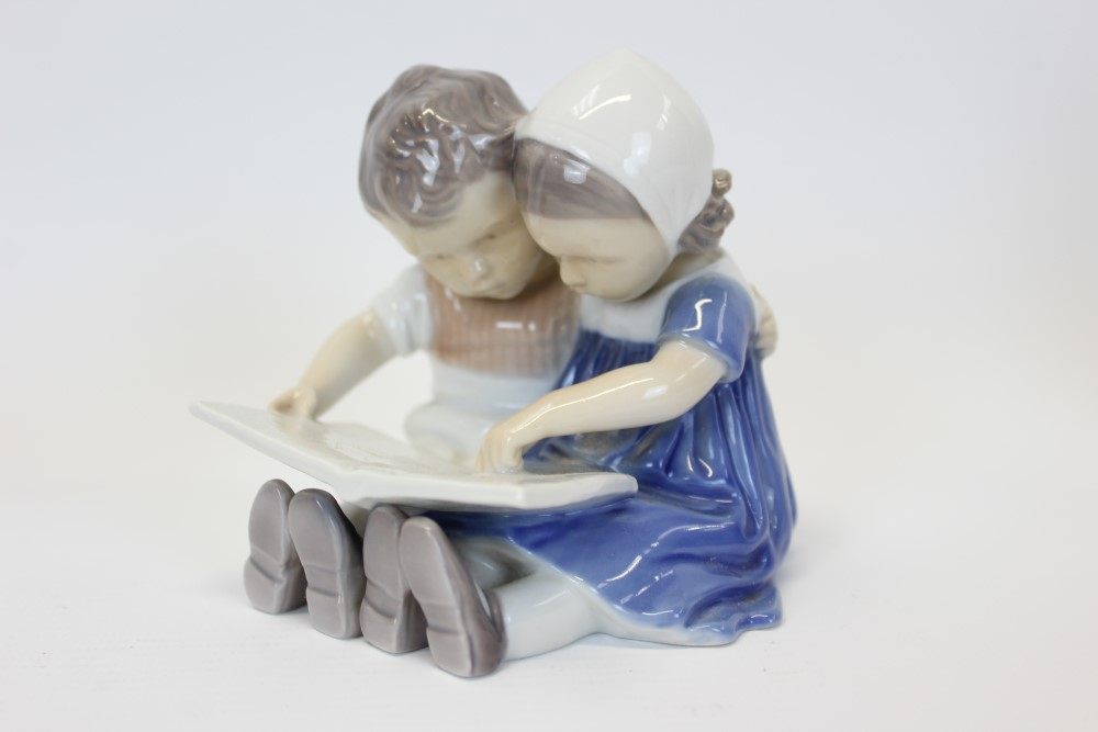 Lot 2043 - Royal Copenhagen porcelain figure - girl holding doll,