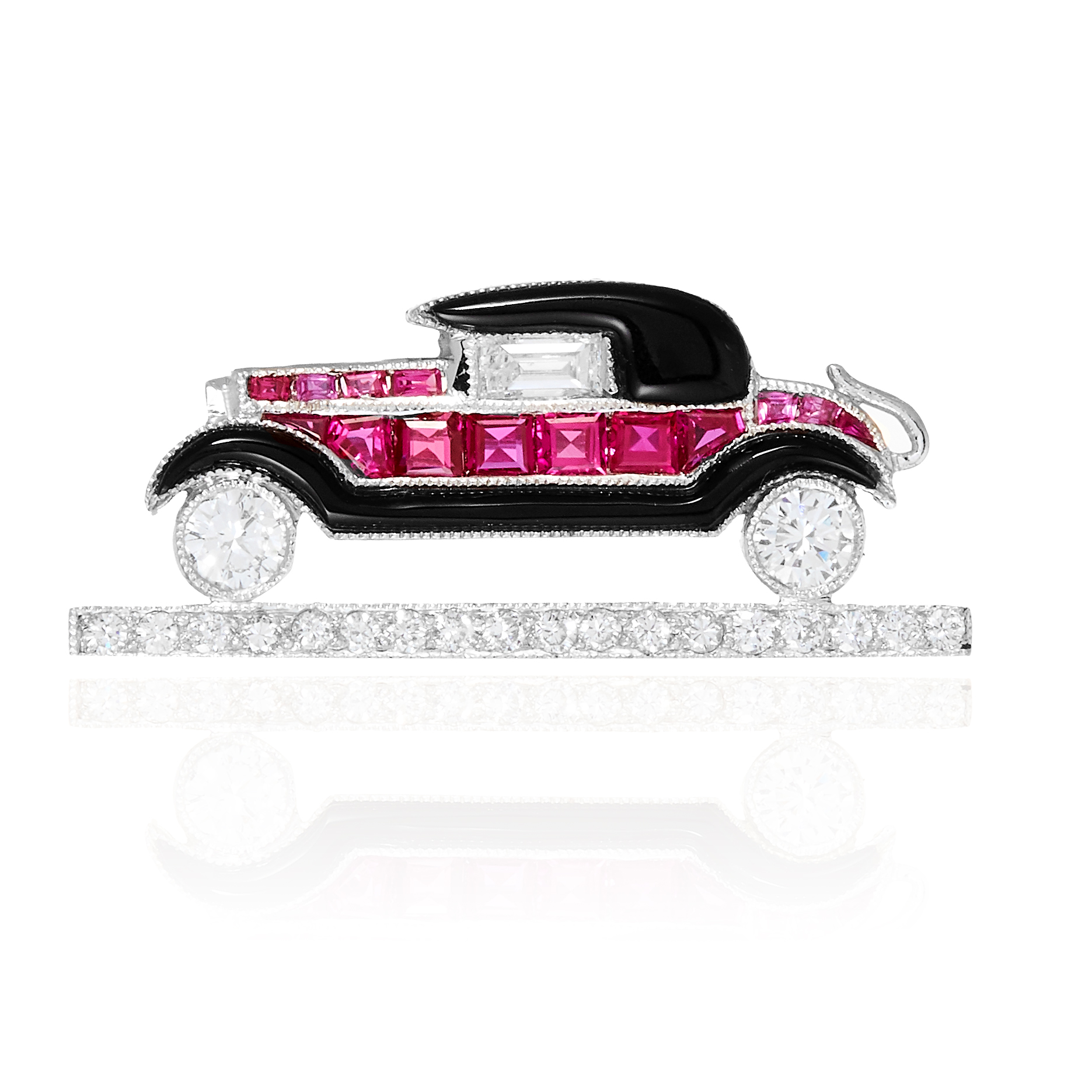 AN ONYX, RUBY AND DIAMOND CAR BROOCH in gold or platinum, jewelled with round cut diamonds,