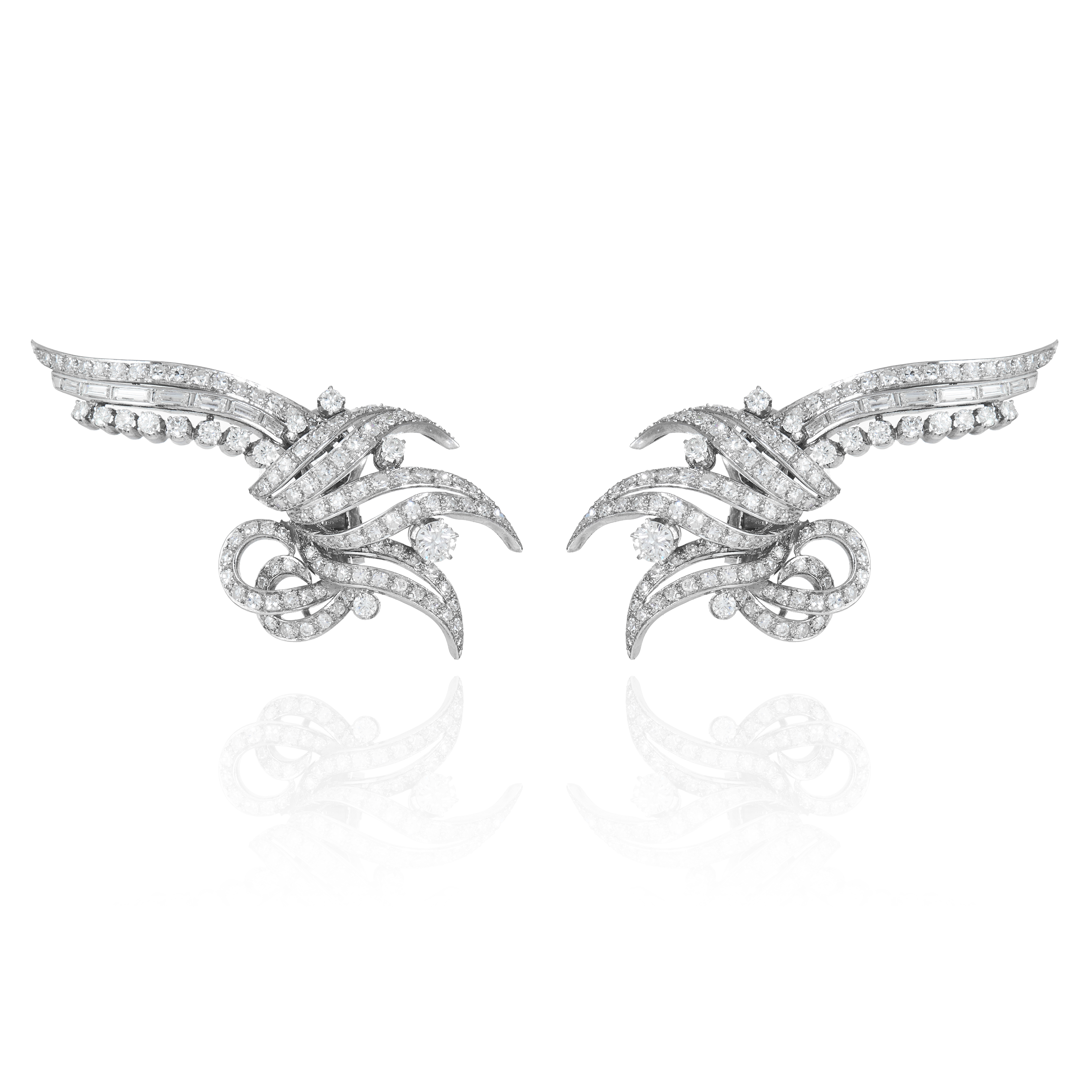 A PAIR OF VINTAGE DIAMOND EARRINGS in gold or platinum, in scrolling motif, jewelled with round