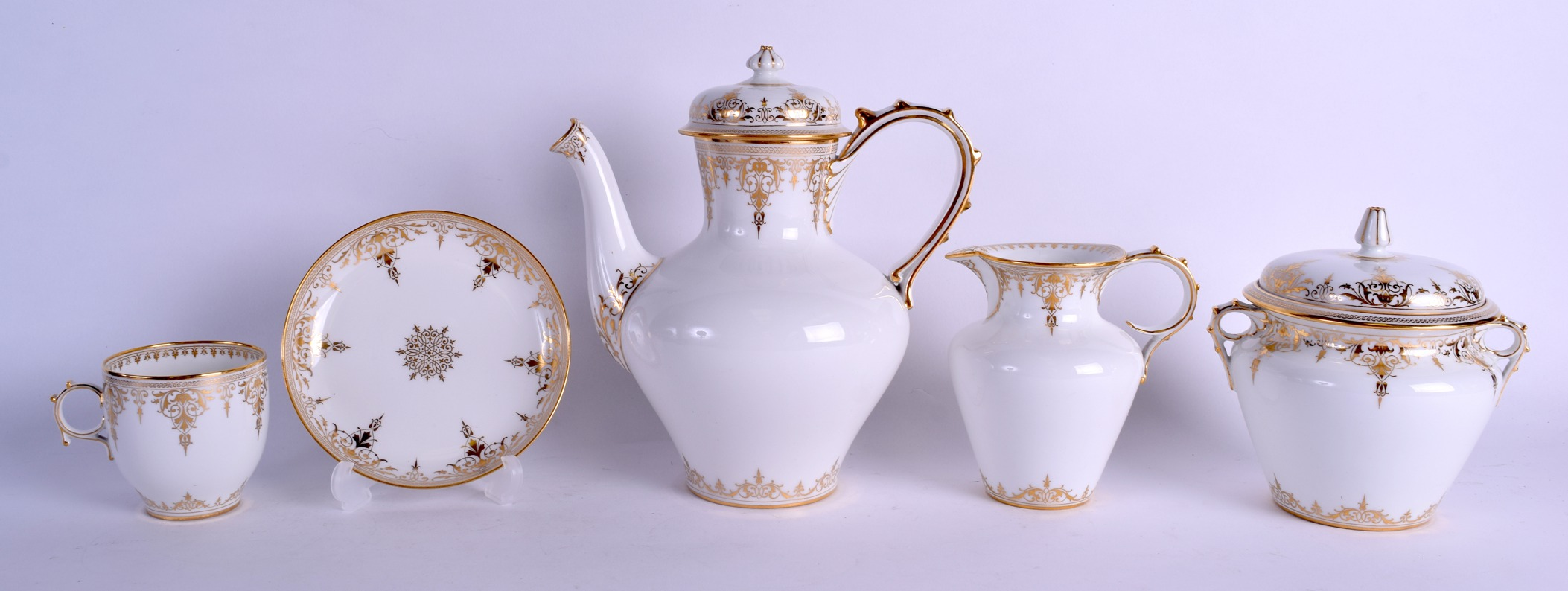 Lot 60 - A GOOD CASED 19TH CENTURY FRENCH SEVRES PORCELAIN TEASET painted with rich gilt scrolling foliage.