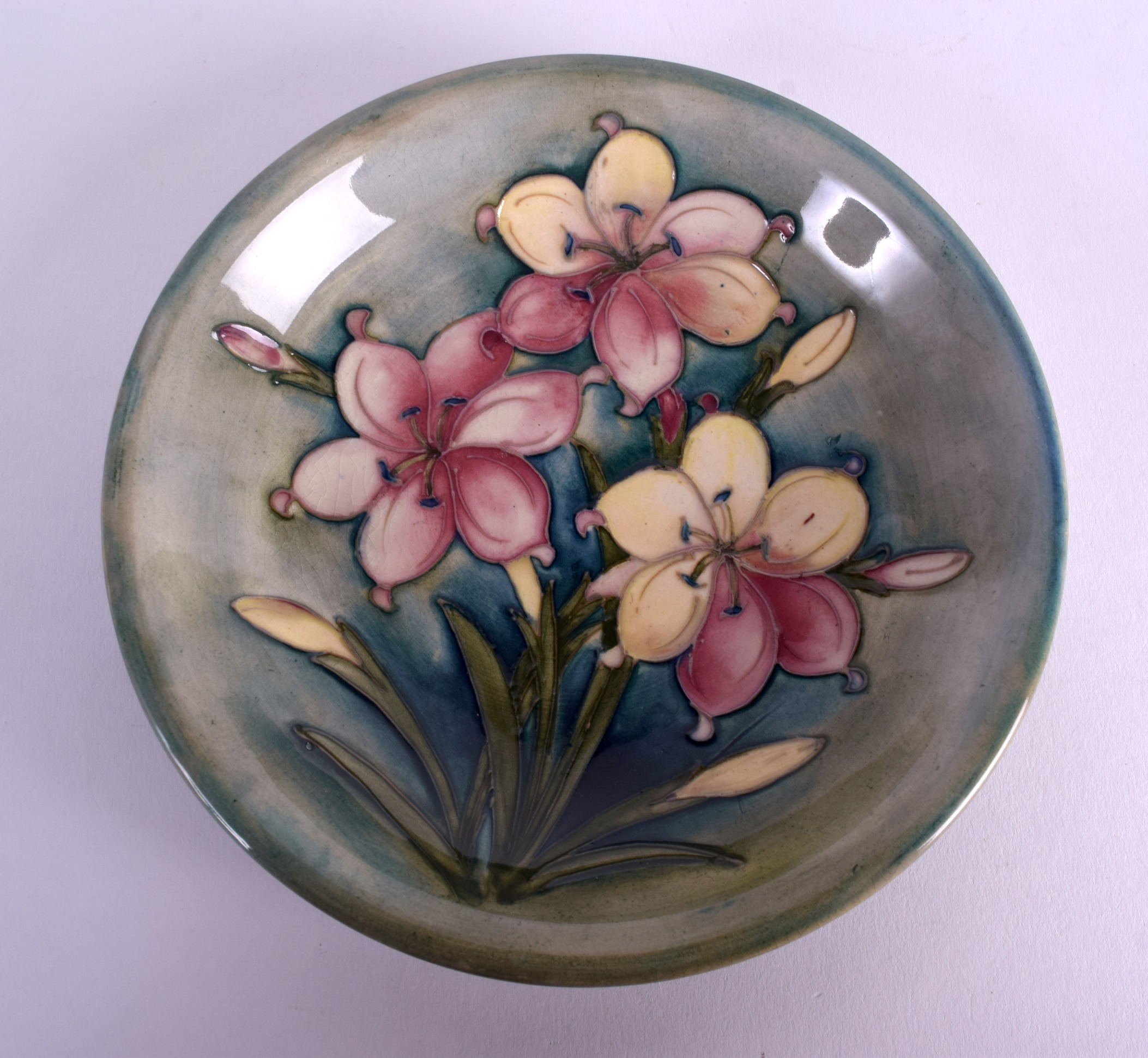 Lot 89 - A WILLIAM MOORCROFT CIRCULAR DISH decorated with three floral sprays. 18 cm diameter.