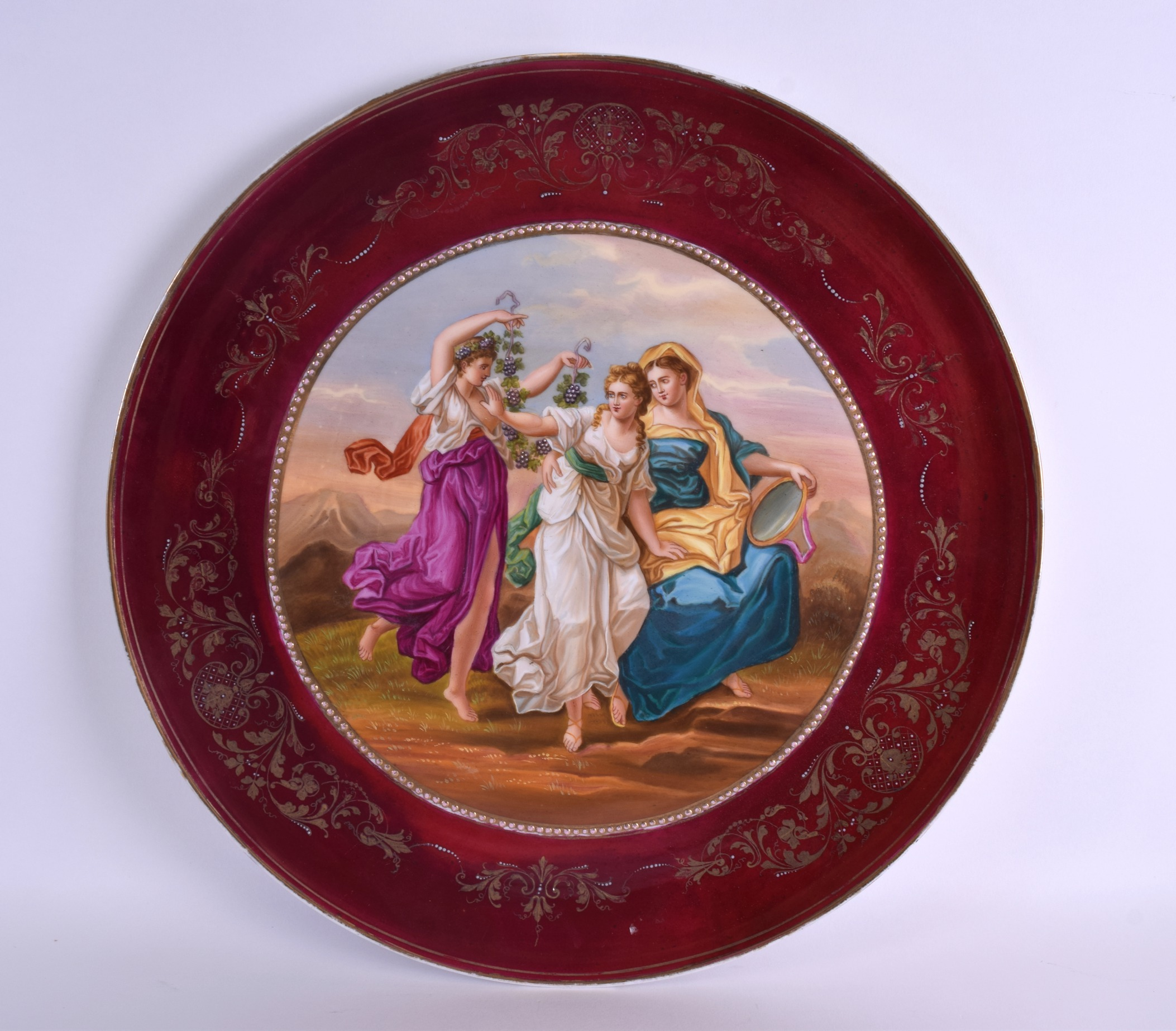 Lot 91 - A LARGE EARLY 20TH CENTURY VIENNA PORCELAIN CHARGER painted with three classical females within a