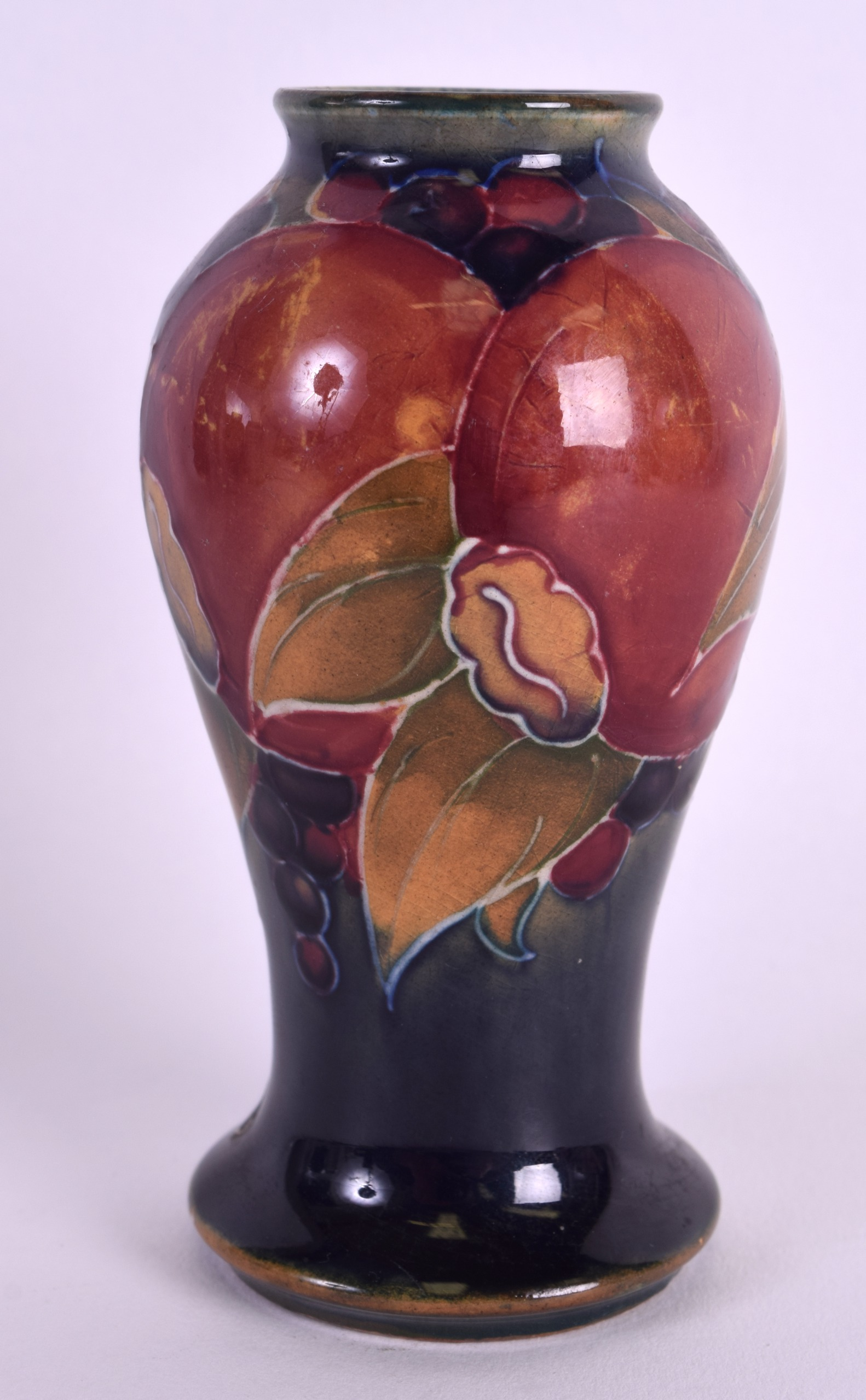 Lot 106 - A SMALL WILLIAM MOORCROFT BALUSTER VASE decorated with pomegranate. 9.75 cm high.