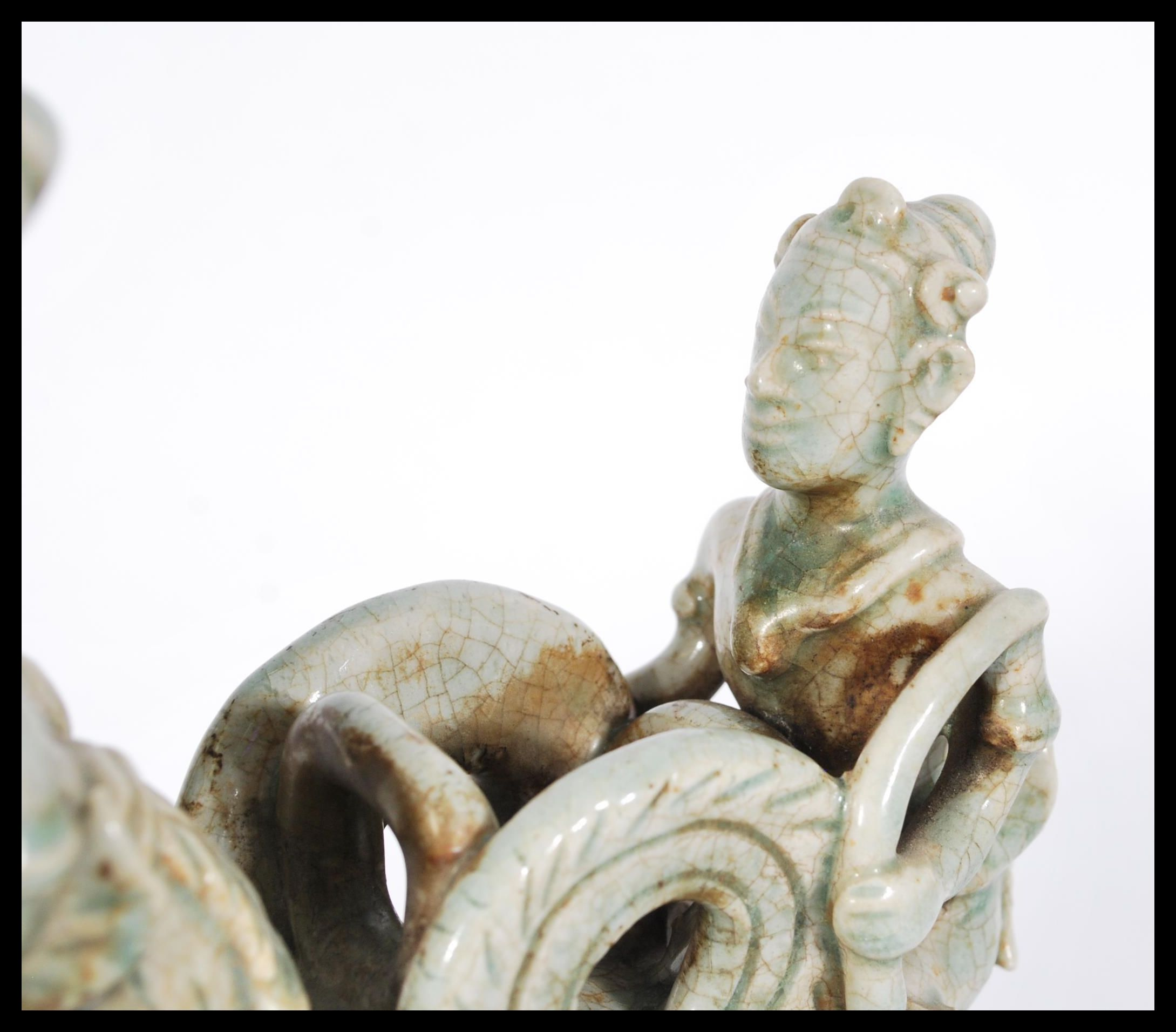Lot 347 - A 20th century Asian Cambodian ceramic figure group with a mint crackle glaze on a rectangular