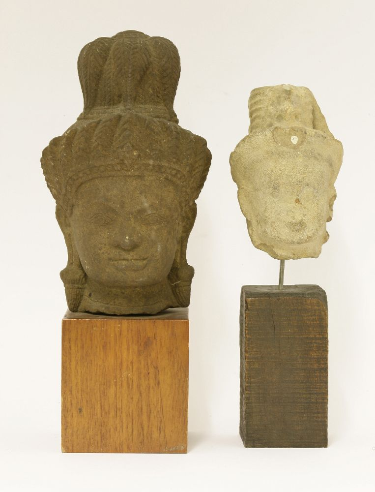 Lot 553 - Two stone carvings of heads of a bodhisattva, Cambodian, each wearing a tall hat with jewels, fitted