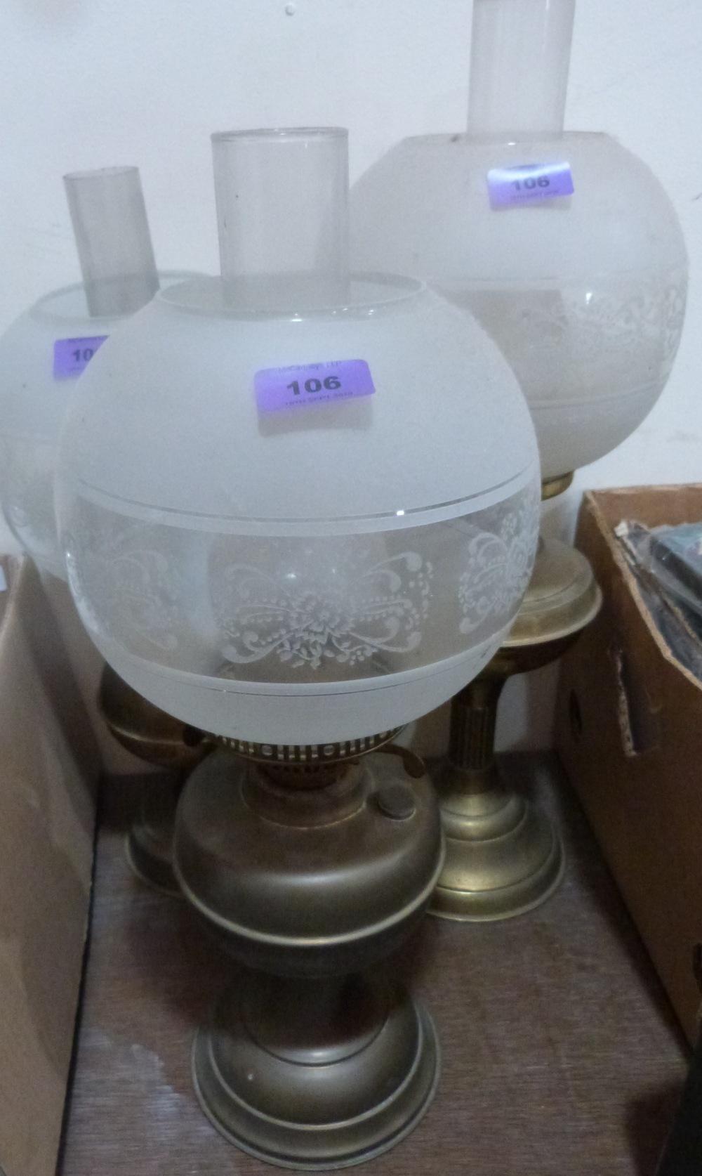 Lot 106 - Three brass oillamps