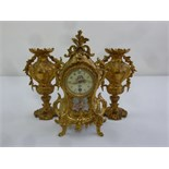 Lot 401 - A French 19th century gilded metal mantle clock with porcelain panels and vase form garnitures